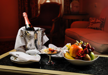 Romantic evening with bottle of champagne, sweets and fruits