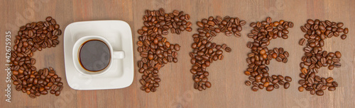 The word Coffee spelled with hundreds of coffee beans and one cu