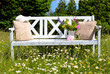 weiße Gartenbank auf einer Blumenwiese