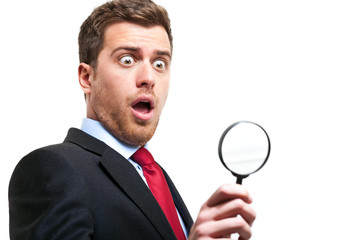surprised business man looking through loupe