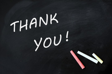 Thank you written with chalk on a smudged blackboard