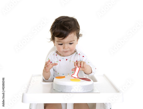Baby eating his first birthday cake