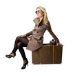 Beautiful blond woman with suitcase, dressed in retro style