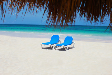 Pair of chairs on a white sandy beach