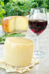 forma di pecorino sardo e bicchiere di vino rosso