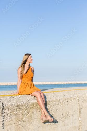 Frau sitzt an Betonmauer