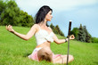 Beautiful woman meditates on green lawn
