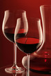 Two glasses of red wine and decanter on red background