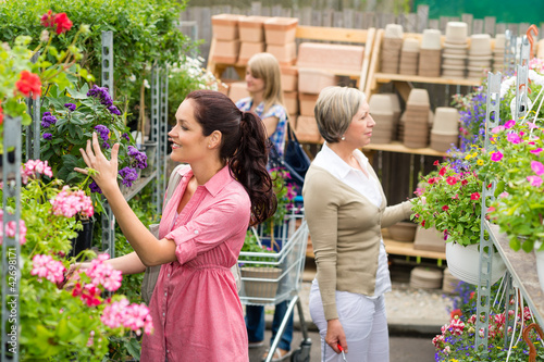 Woman taking potted plant at garden center