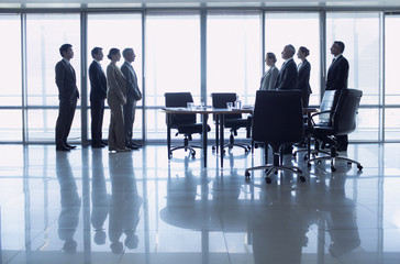 Separate groups of business people facing off in conference room