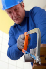 Tradesman cutting a tube with a saw