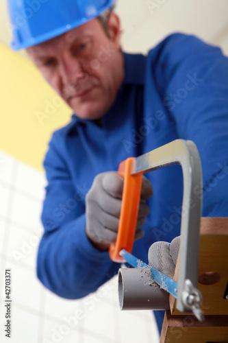 Tradesman cutting a tube with a saw