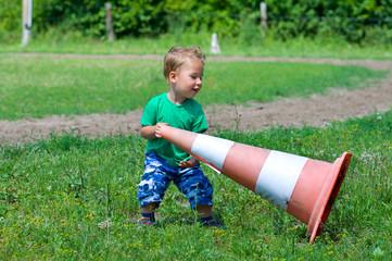 Kleiner Junge wirft Verkehrshütchen um