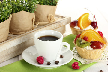 cup of coffee and sweet cakes with fruits on wooden table