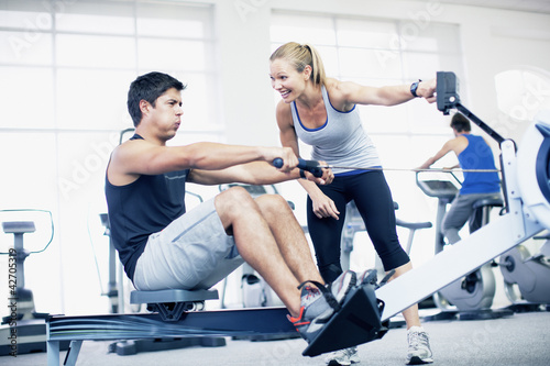 Personal trainer with man on rowing machine in gymnasium