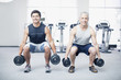 Men doing squats with dumbbells in gymnasium
