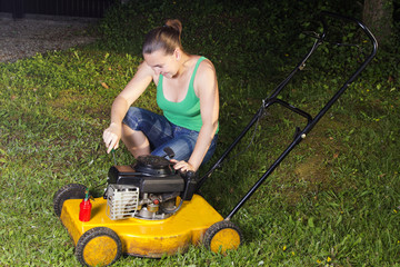 Smiling sexy girl oiling and repairing yellow lawn mover
