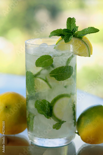 A glass of mojito/ caipirinha  with lime slices and mint