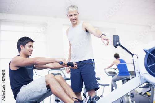 Personal trainer guiding man on rowing machine in gymnasium