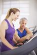 Man helping woman on treadmill in gymnasium