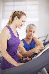 Man helping woman on treadmill in gymnasium