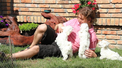 Happy man playing with a maltese puppy