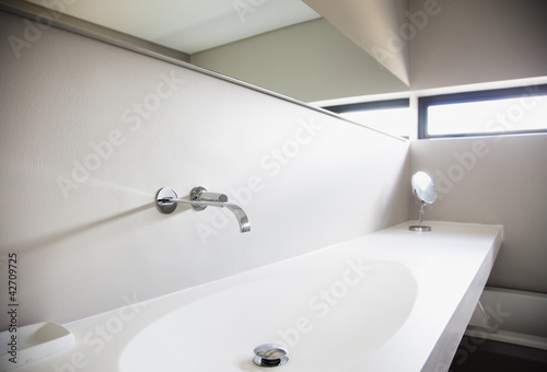 Sink and long mirror in modern bathroom