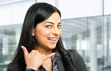 Smiling young businesswoman gesturing to call