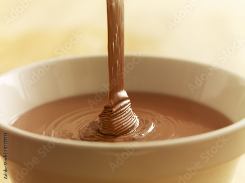 Close up of chocolate syrup pouring into bowl