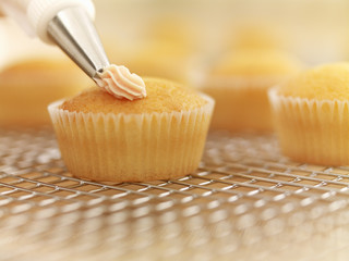 Close up of cupcakes being frosted