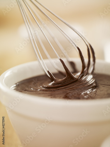 Close up of wire whisk dipping in bowl of melted chocolate