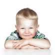 Portrait of a cute little boy smiling while sitting at table, is