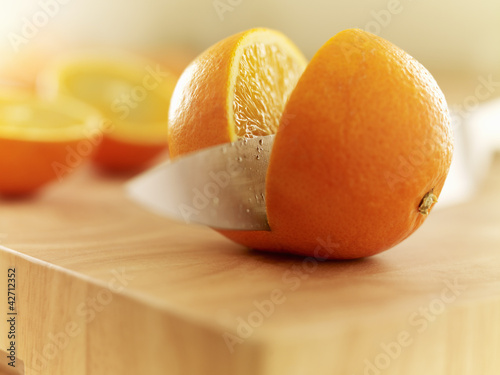 Knife slicing orange on cutting board