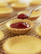 Close up of jam being scooped into baked tarts
