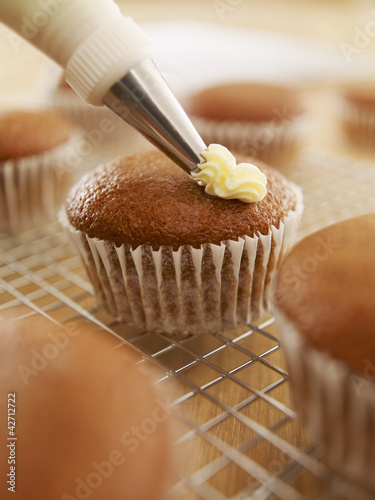 Close up of cupcake being frosted