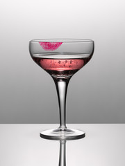 Close up of pink champagne in glass with lipstick stain