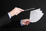Music conductor hands with baton and notes isolated on black