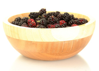 Wooden bowl with ripe mulberries isolated on white close-up