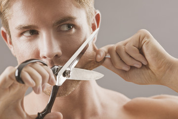 Portrait of man holding scissors and pulling skin on face