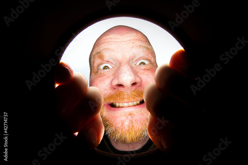 Funny bald man looking down a hole