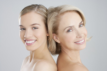 Portrait of smiling mother and daughter back to back