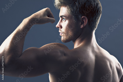 Rear view portrait of man flexing biceps muscles