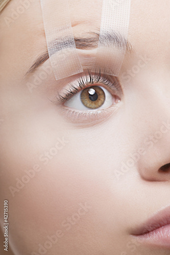 Close up of womanís eye taped open
