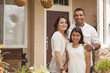 Small Hispanic Family in Front of Their Home - 42718131