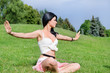 attractive youngl woman meditates on green lawn