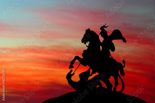 Saint George and the Dragon on sunset background