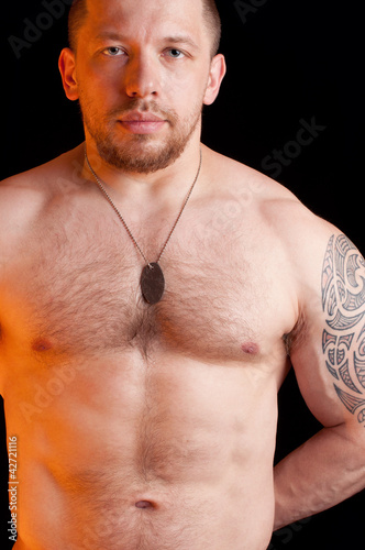 Portrait of an adult shirtless soldier with dog tags