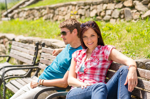 Young couple relaxing on bench in park