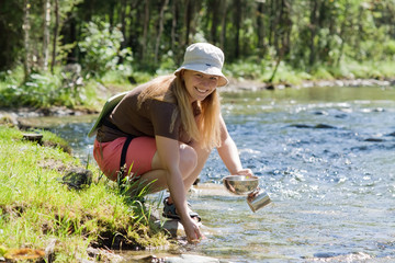 tourist washing utensil in  river