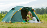 Camping happy woman front of tent